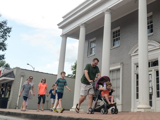 A family walks by the former BB&T bank building at