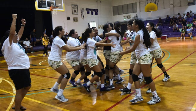 In this file photo, the George Washington High School Geckos celebrate after their 17th annual Shieh Invitational Volleyball Tournament win over the Notre Dame Royals at the George Washington High School gym in Mangilao on Aug. 14.