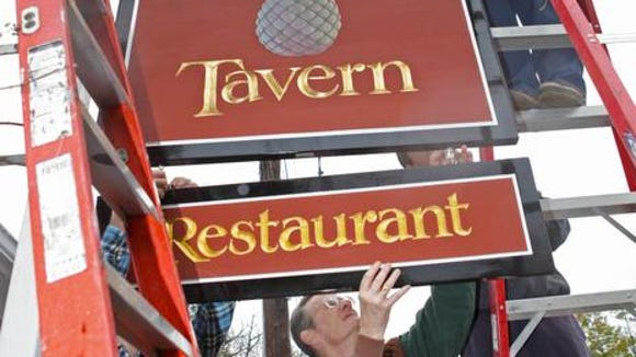 Co-owner Coley DuPont, helps direct the positioning of the Buckley's Tavern sign as it was be hung for the 2012 re-opening.