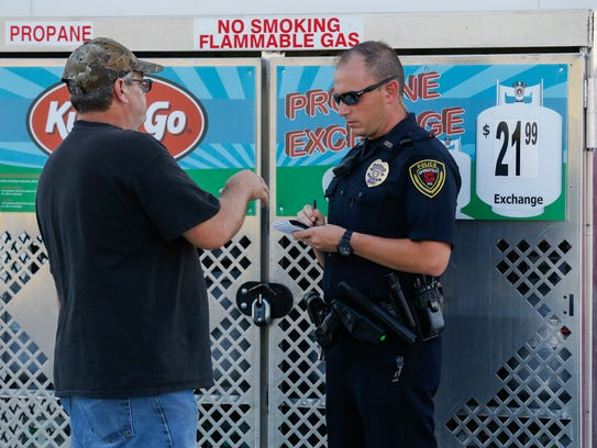 A police officer talks with a witness at the scene