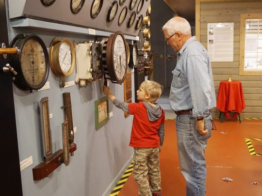 Visitors check-out the equipment in an exhibit simulating the engine room of a ship at the Door County Maritime Museum.