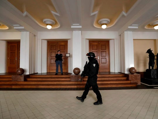 A prison guard walks outside a courtroom in Prague