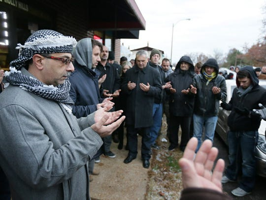 Zuhdi Masri, left, prays for murder victim Zemir Begic