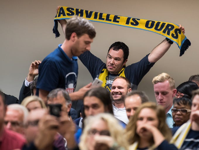 Soccer fans celebrate after a vote on a MLS stadium