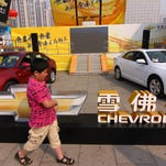 A young Chinese boy walks past Chevrolet cars of GM (General Motors) during a show in Xiangyang city, central Chinas Hubei province, 2 October 2012.  General Motors Co, the biggest foreign automaker in China, said sales in the nation rose 1.7 percent in September, the slowest growth in eight months, as deliveries of Buicks and Cadillacs declined. Deliveries of cars and minivans climbed to 244,266 units in September, the Detroit-based automaker said in a statement on its website. That compares with a 7.3 percent gain for deliveries in August. Sales of Buick cars fell 1.8 percent in September after climbing 2.8 percent in August, while Cadillac sales dropped 8.3 percent last month, GM said.