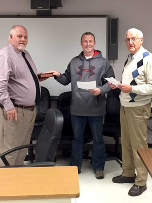 Derek Cathell (center) is sworn in by Superintendent Mark Steele (left) and Board of Education President Charles Bireley.