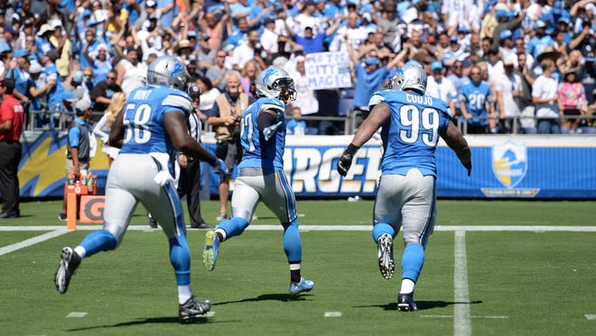 Detroit Lions safety Glover Quin (27) is congratulated by defensive tackle Jermelle Cudjo (99) and defensive end Phillip Hunt (58) after scoring a touchdown on an interception return against the San Diego Chargers at Qualcomm Stadium.