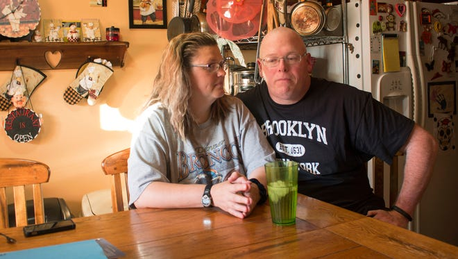 In this Friday, July 7, 2017, photo, Tammie Jackson, and her husband, Travis Jackson of Butte, Mont., discuss their Medicaid program benefits at their home in Helena, Mont. Tammie, who was uninsured until she enrolled in Montana's expanded Medicaid program, receives medical care for a host of health issues, including a back injury that has kept from returning to her job cleaning hotel rooms. Montana officials who tout the dramatic drop in the state's medically uninsured due to expanded Medicaid, are now under pressure to reduce the number of new Medicaid enrollees.