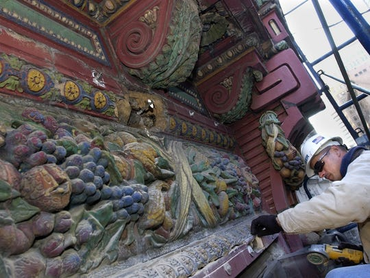 Wyndell Rogers, an employee of Zeiser Construction Co. in  East Price Hill, grinds cracks for preparation of a sealant as he works on the decorative Rookwood terra cotta tiles on the front facade of the old Gidding Building in 2003.