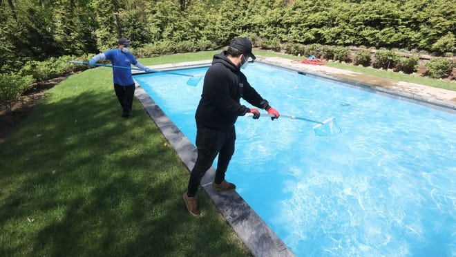 Edwin Rodriguez, left, and Junior Larancuen of Westrock Pools clean a customer's pool in Suffern on May 15.