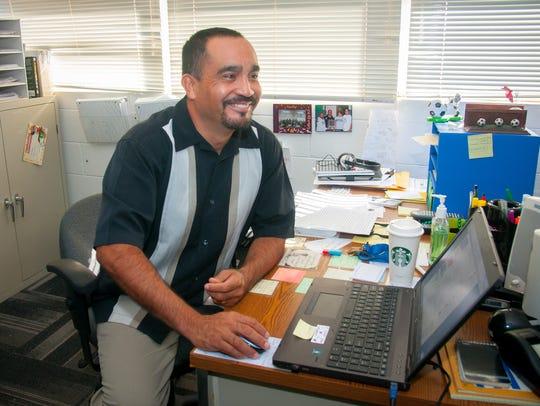 Social Studies teacher David Morales sits at his desk