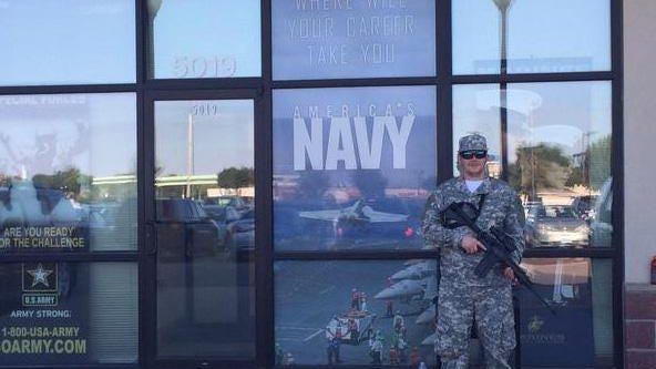 Civilian Roy Cooper stands guard outside the Armed Forces Recruiting Center in Sioux Falls to protest a lack of armed employees at the center.