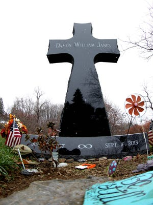 The headstone for Damon Janes, a high school football player who died in 2013, is a cross that is six feet tall.