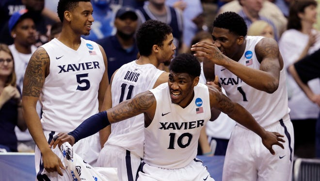"Xavier players, from left, Trevon Bluiett (5), Remy Abell (10), Dee Davis (11), and Jalen Reynolds (1) celebrate their 75-67 win over Georgia State during an NCAA tournament third round basketball game Saturday, March 21, 2015, in Jacksonville, Fla.  Xavier will play Michigan in the ""Gavitt Games"" on Nov. 20, 2015."