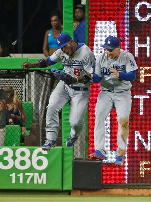Los Angeles Dodgers left fielder Yasiel Puig, left, celebrates with center fielder Joc Pederson after Puig caught a ball hit by Miami Marlins' Martin Prado during the seventh inning of a baseball game, Saturday, Sept. 10, 2016, in Miami. Puig, brought back from the minors on Sept. 2, made an outstanding diving catch for the final out of the seventh. Prado hit a drive to deep left-center, and Puig sprinted and as he approached the warning track dived toward the wall to make the catch. The Dodgers defeated the Marlins 5-0. (AP Photo/Wilfredo Lee) ORG XMIT: FLWL111