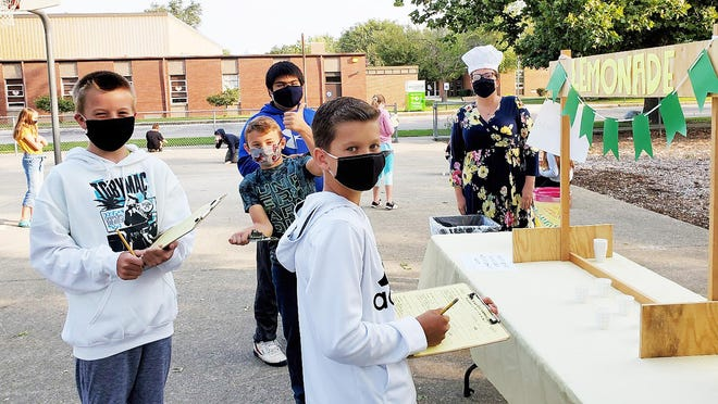 Sixth grade teacher Katie Taylor is ready to serve up some ice-cold lemonade while Landon Meiss, Mason Fehr, Rustin Slagel and Cristian Medina record their observations and recipe information.