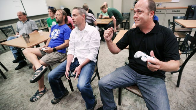 Win Norton, founder and chief technology officer for Healthx (right), cheers  as he and his engineering staff play video games during   lunch break at their office on Priority Way West Drive in Indianapolis .  .