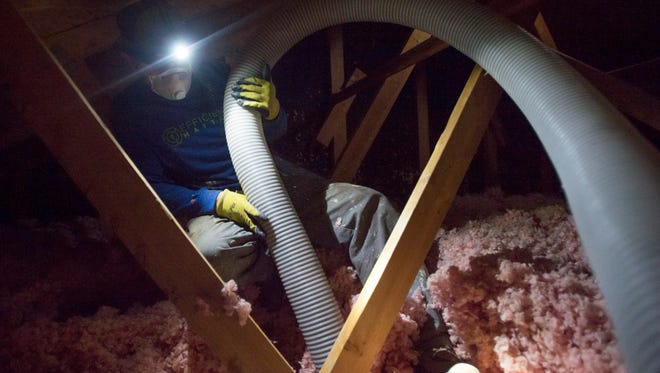 Jeff Davis with Efficiency Matters removes old insulation from the attic of a Fort Collins home Wednesday, Dec. 21, 2016. The material is replaced with more energy-efficient foam to combat heating and cooling loss in the home.