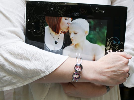 Laura Covington holds a photo of herself and her daughter