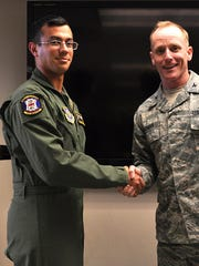 Col. Patrick Rhatigan, 19th Airlift Wing commander, congratulates Airman 1st Class Jeremy Jutba-Hake, a 53rd Airlift Squadron C-130 E/H loadmaster, for his selection as Combat Airlifter of the Week Oct. 28, 2013, at Little Rock Air Force Base, Ark. Jutba-Hake collapsed following a training exercise at Andersen Air Force Base, according to an Air Force press release from Dec. 15, 2015.