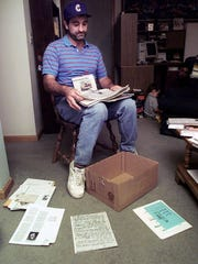 Rod Dion looks through newspaper clippings after his