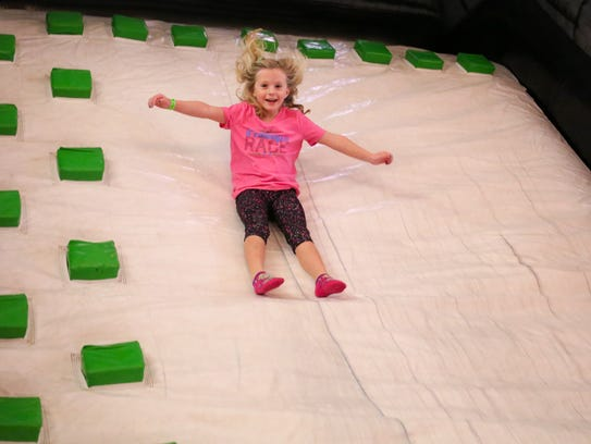 Julie Simonetti, slides down an inflatable slide Saturday