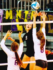PCA's Grace Kellogg (middle), who had 21 kills, tips the ball past Leland's Jessica Paulson (left) and Devon Burns.