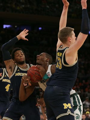 Michigan guard Zavier Simpson (3) and Moritz Wagner defend against Michigan State forward Jaren Jackson Jr. (2) during the first half of a semifinal game of the 2018 Big Ten Tournament at Madison Square Garden.