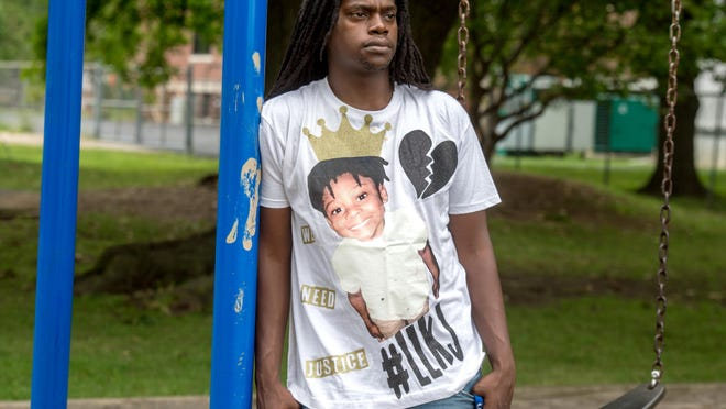Scottie Ward wears a T-shirt calling for justice for his murdered son Jeremiah Ward and #LLKJ, which stands for Long Live King Jeremiah, on the playground at the Franciscan Recreation Complex in Peoria. Jeremiah was four years old when he was shot to death May 13, 2019 in the parking lot of Lincoln Terrace Apartments in Peoria.