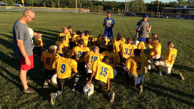 Derrick Vorhis, head coach of the junior Small Fry Football team, reviews lessons learned from a recent scrimmage with Groton. The team is made up of 26 nine- and 10-year-old players.