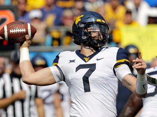 FILE - In this Sept. 1, 2018, file photo, West Virginia's Will Grier (7) looks to pass against Tennessee in the first half of an NCAA college football game, in Charlotte, N.C. Grier is married with a young daughter. (AP Photo/Chuck Burton, File)