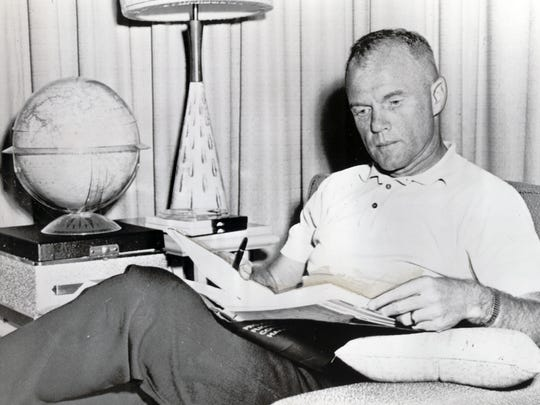 FEBRUARY 14, 1962: Astronaut John Glenn reads a Project Mercury flight manual as he waited at the Cape Canaveral missile test center for scheduled orbital launching tomorrow, 2/15/62. Rough weather in the recovery areas is now causing concern about tomorrow's attempt to put him in orbit around the Earth.