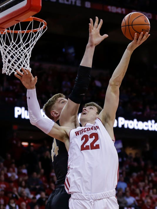 FILE - In this Feb. 15, 2018, file photo, Wisconsin's Ethan Happ (22) shoots against Purdue's Isaac Haas (44) during the second half of an NCAA college basketball game, in Madison, Wis. Happ was picked to the AP All-Big Ten Team, announced Wednesday, Feb. 28, 2018, in voting by 12 journalists covering the conference. (AP Photo/Andy Manis, File)