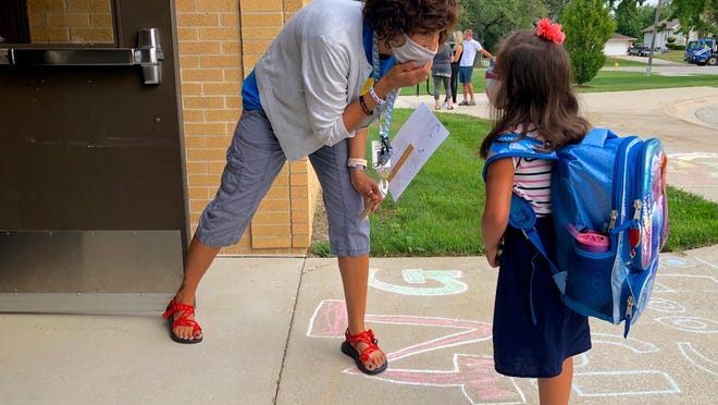 Special Education Paraprofesional Dawn Ward at New Groningen Elementary in Zeeland helps a student find her classroom on the school's first day of class Tuesday, Sept. 1. Gov. Gretchen Whitmer issued a new order Friday that requires the state's youngest students to wear a mask while attending face-to-face class.