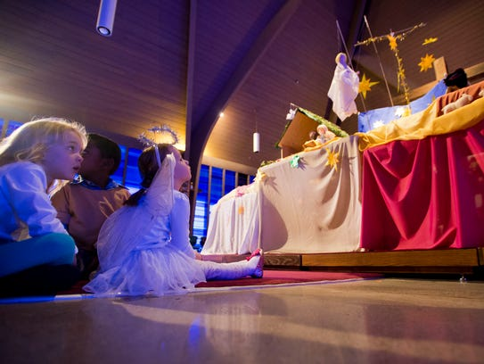 Kids watch a puppet pageant during a Christmas Eve