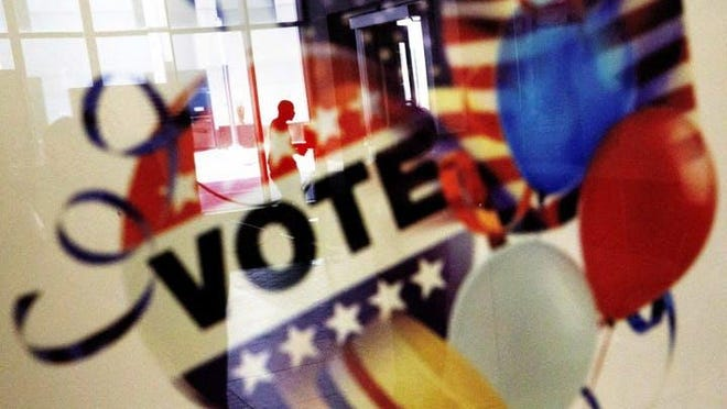In this Nov. 1, 2016, photo, a voter is reflected in the glass frame of a poster while leaving a polling site in Atlanta, during early voting ahead of the Nov. 8 election day.