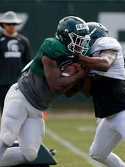 Michigan State running back La'Darius Jefferson, left, and linebacker Tyriq Thompson run a drill during an NCAA college football practice, Monday, Aug. 12, 2019, in East Lansing, Mich. (AP Photo/Al Goldis)