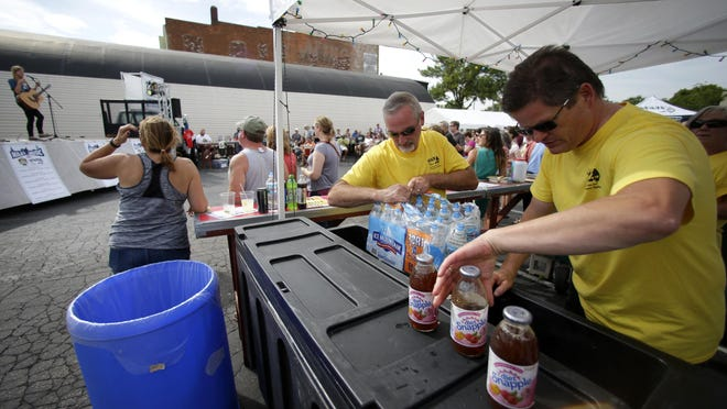 Volunteer John McClellan helps Spats owner Bill Neubert fill a cooler with water while Jordin Baas performs during the first day of the Mile of Music festival last Thursday in Appleton.