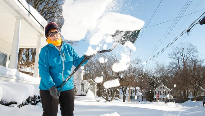 Irene Voce of Suffern throws snow as she clears her walkway on Sunday.