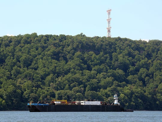 A barge is parked in the Hudson River, across from the City of Yonkers, under the Alpine tower, Aug. 8, 2016.