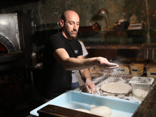 Owner and Chef of Razza, Dan Richer, sprinkles flour on dough, as he prepares pizza, Tuesday, March 6, 2018, in Jersey City.