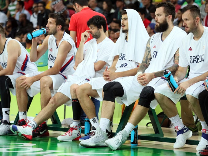 The Serbia bench reacts against USA in the men's basketball