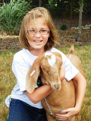 Grace Draeger holds her goat Neville in the yard of the family farm.