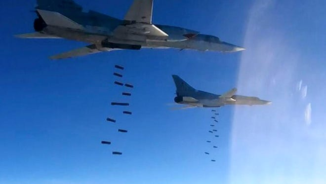 In this photo provided by the Russian Defense Ministry Press Service shows Russian air force Tu-22M3 bombers strike the Islamic State targets in Syria, Monday, Jan. 23, 2017. The air raid targeted the IS around Deir el-Zour in eastern Syria where the IS has launched an offensive against Syrian government forces.
