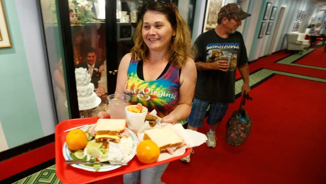 Amy Eggleston carries a tray of food as she and Jarrod Copenhaver of White Sulphur Springs, head back to their room at the Greenbrier Resort in White Sulphur Springs, W. Va., June 28, 2016. The two were flood victims when their roof leaked and ruined all their belongings. The hotel provided a free room and meals to the couple.