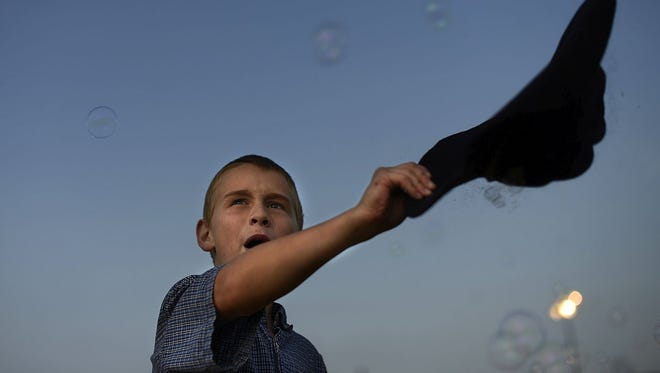 Kordell Hansen, 10, tries to catch bubbles with his cowboy hat during The Kiddie Karnival in downtown Green Bay on Tuesday.