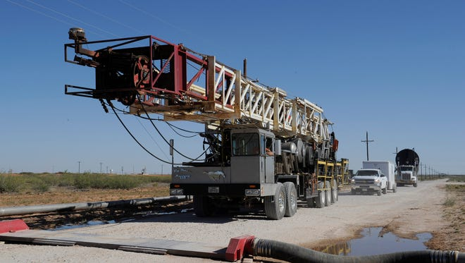 A drilling rig used for hydraulic fracturing is trucked across a water hose at a drill site last month in Midland, Texas.