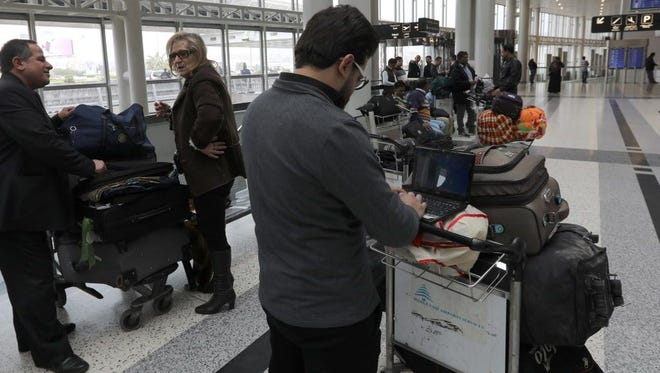A Syrian passenger traveling to the United States through Amman types on his laptop before entering Beirut international airport's departure lounge on March 22, 2017.