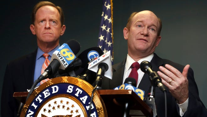 U.S, Sen. Chris Coons, D-Del., right, speaks alongside U. S. Sen. Pat Toomey, R-Pa., during a press conference, Monday, March 5, 2018, in Philadelphia. Toomey and Coons say they'll introduce a bill Monday that will require federal authorities to notify states when a felon or a fugitive attempts to buy a firearm but fails the National Instant Criminal Background Check System.