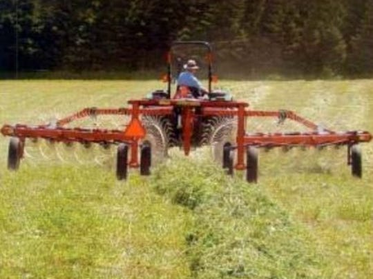 A wheel rake merges two swathes of alfalfa into one windrow.